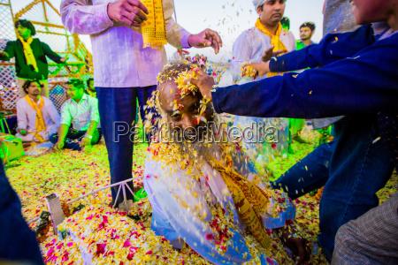 guru getting flower petals thrown over
