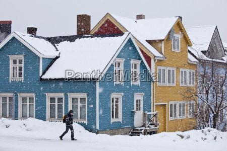 man walks past traditional wooden buildings