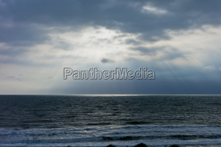 suns rays over rough sea at