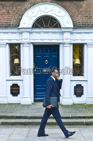 businessman using cellphone passes traditional doorway