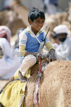 boy jockey camel racing with walkie