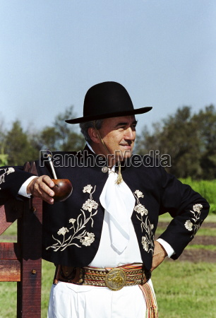 gaucho in traditional costume drinking local