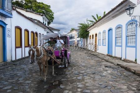 horse cart with tourists riding through
