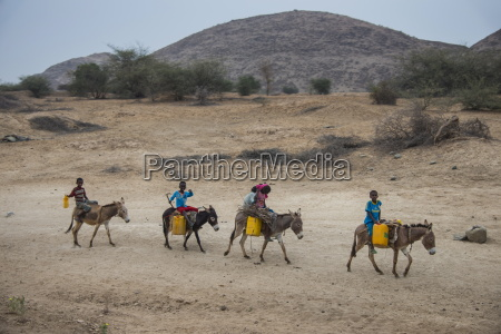 young kids riding on donkeys to