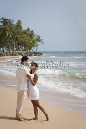 hispanic romantic couple dressed in white