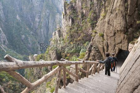 mature asian couple descend concrete steps