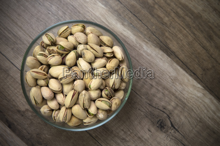 glass bowl of pistachios on wooden