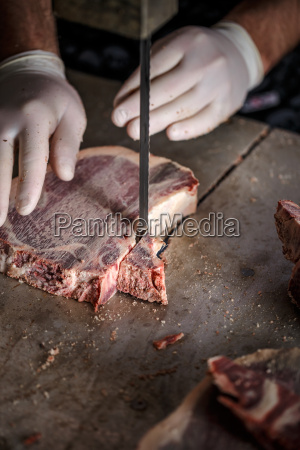 butcher is slicing meat