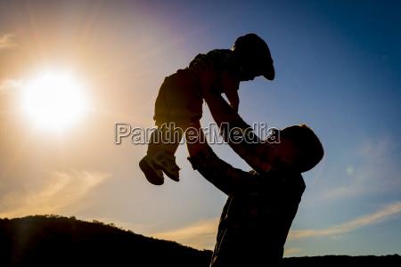 usa texas father holding son aloft