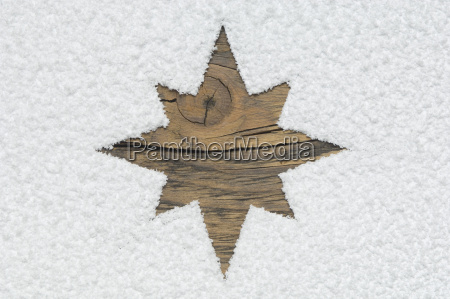 carved christmas star on wooden board