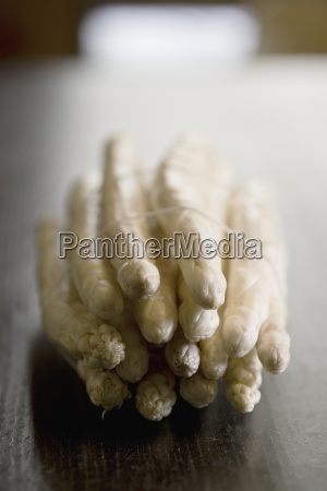 bundle of white asparagus on wooden