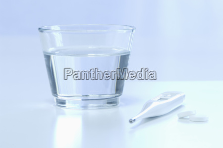 clinical thermometre with glass of water