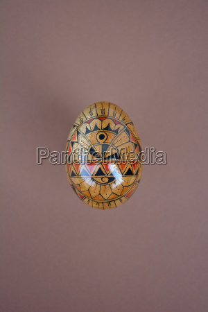 painted wooden egg on brown background
