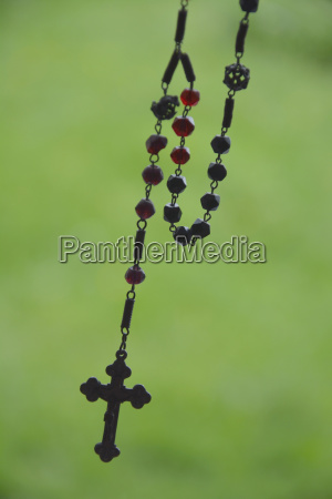 rosary in front of blurred green