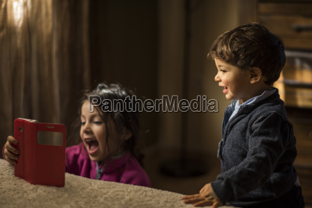 little siblings with smartphone on sofa