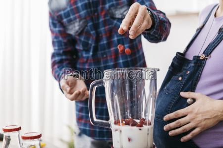 couple preparing smoothie with raspberries partial