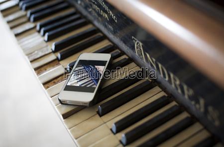smartphone lying on keyboard of old