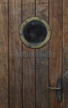 wooden door with porthole of a