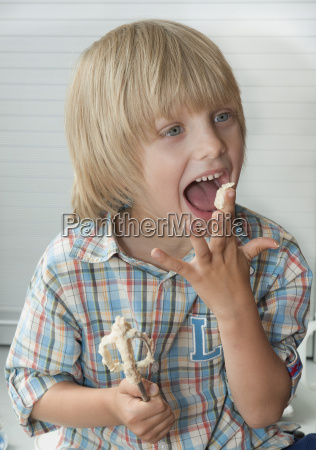 austria boy licking cake dough close