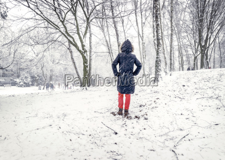 woman standing in snow rear view