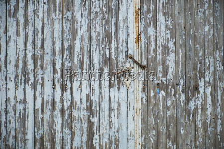 weathered old wooden door with rusty