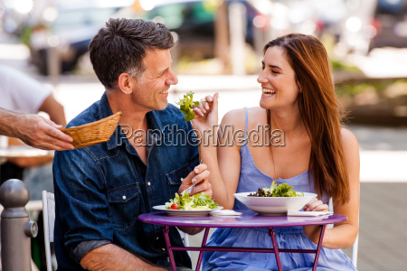 couple enjoying food in a sidewalk