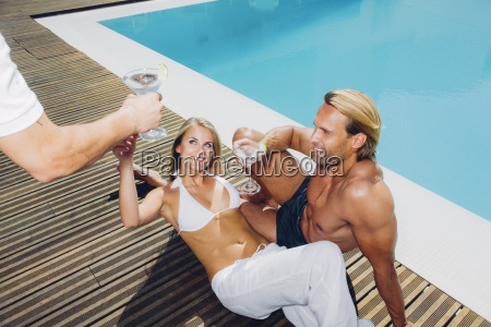 couple at pool edge receiving drinks