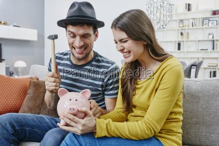 couple in furniture store demolishing piggy