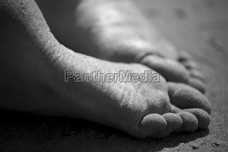two soles of sandy feet close