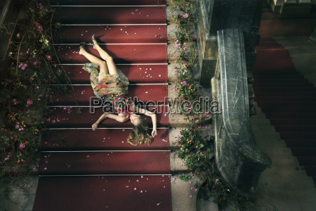 woman lying on stairs with rose