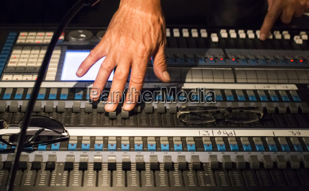 audio engineers hands at mixing console