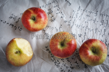 four apples lying on paper with