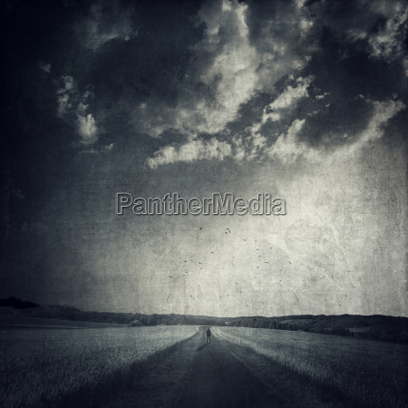 man standing on empty countryl road