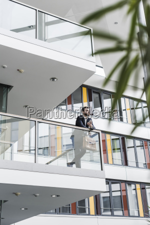 businessman standing on landing of an