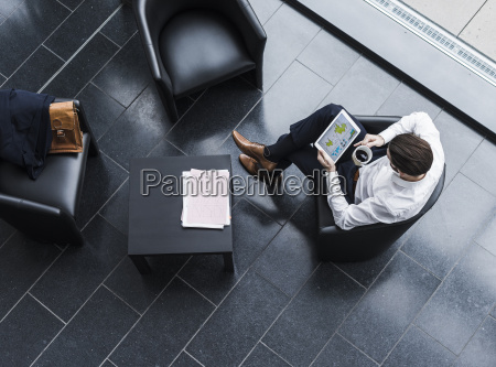 businessman sitting in lobby drinking coffee