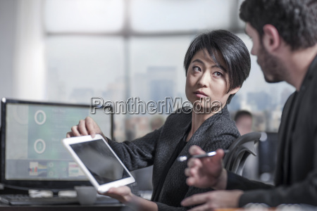 woman showing tablet to colleauge in