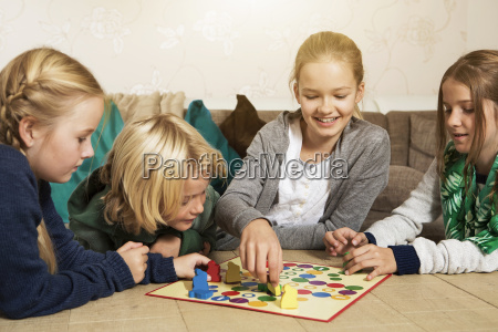four children playing ludo in living