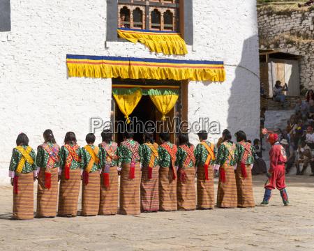bhutan people performing folk dance in