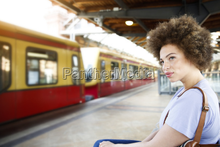 young woman sitting on bench at