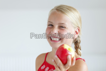smiling blond girl holding an apple