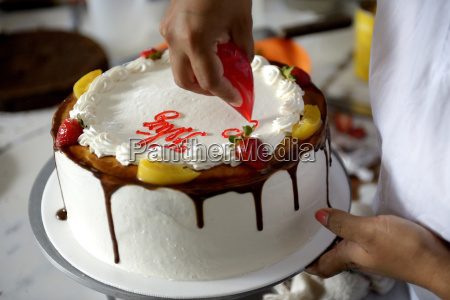 pastry cook decorating cream cake close