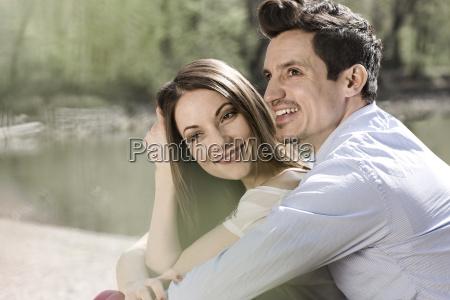 happy couple sitting near water
