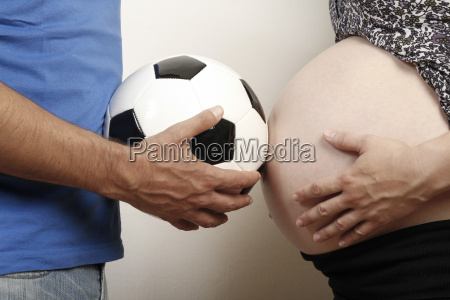 mature man holding soccer ball in