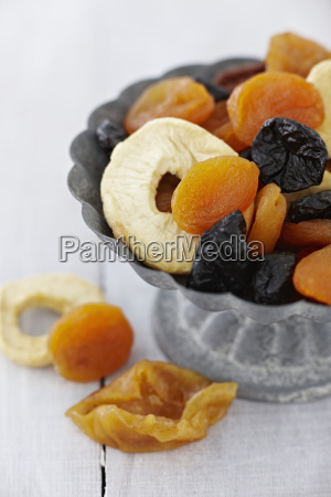 bowl of dried fruits on wooden