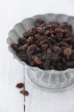 bowl of raisins on wooden table