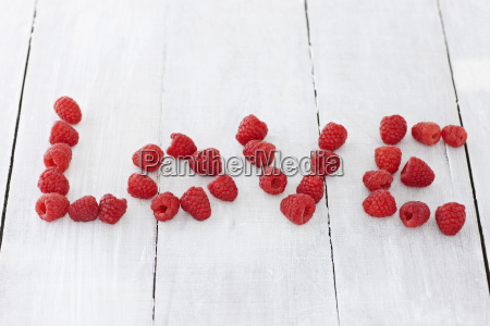 text formed with raspberries on wooden