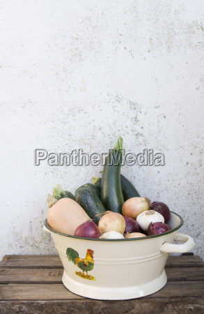 enamel colander of courgettes onions and