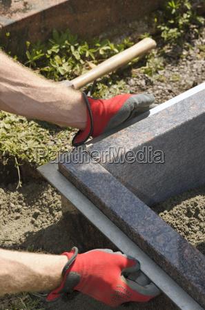 stonemason working on a grave adjusting