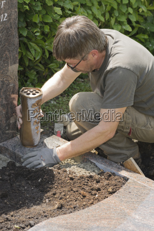 stonemason working on a grave placing
