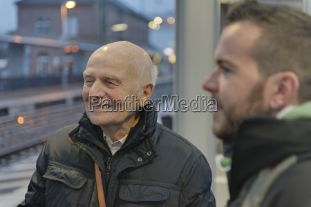 young man and senior man waiting